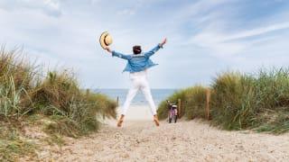 Urlauberin mit Strohhut in den Dünen auf Rügen, Deutschland