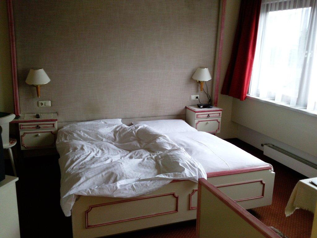 bild bett und tapezierte r ckwand zu landhotel. Black Bedroom Furniture Sets. Home Design Ideas