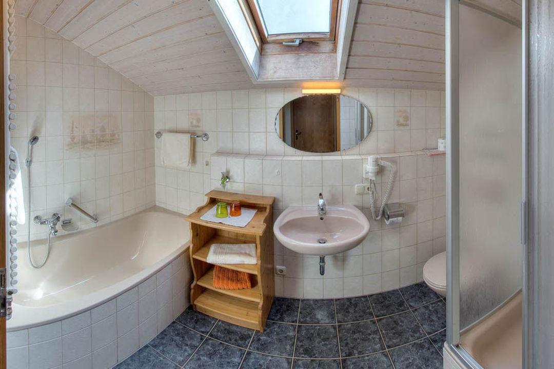 Das Badezimmer mit Badewanne, Dusche und WC.\