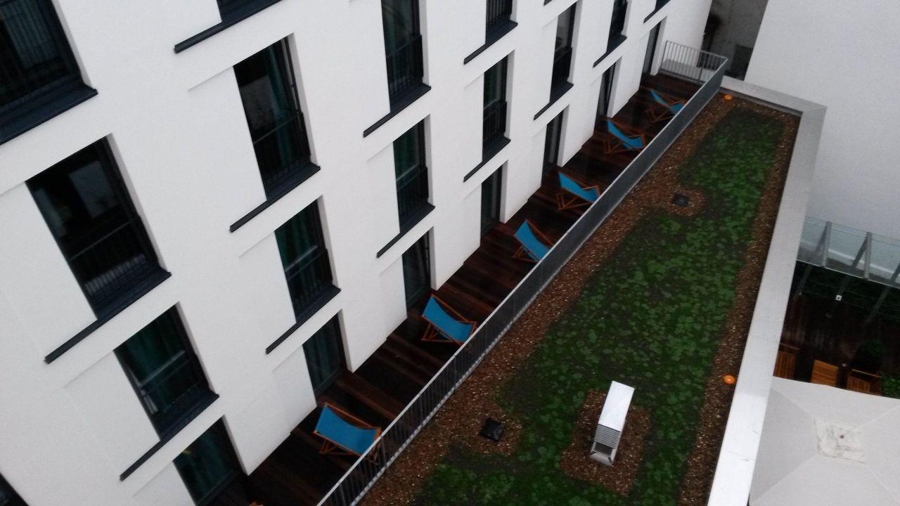 Terrassenzimmer Holzdielen und Liegestuhl\