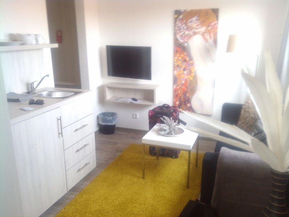 Wohnzimmer mit Kühlschrank, Spüle und Sofa\