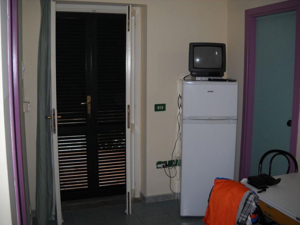 Wohnzimmer mit Kühlschrank und Ferseher\