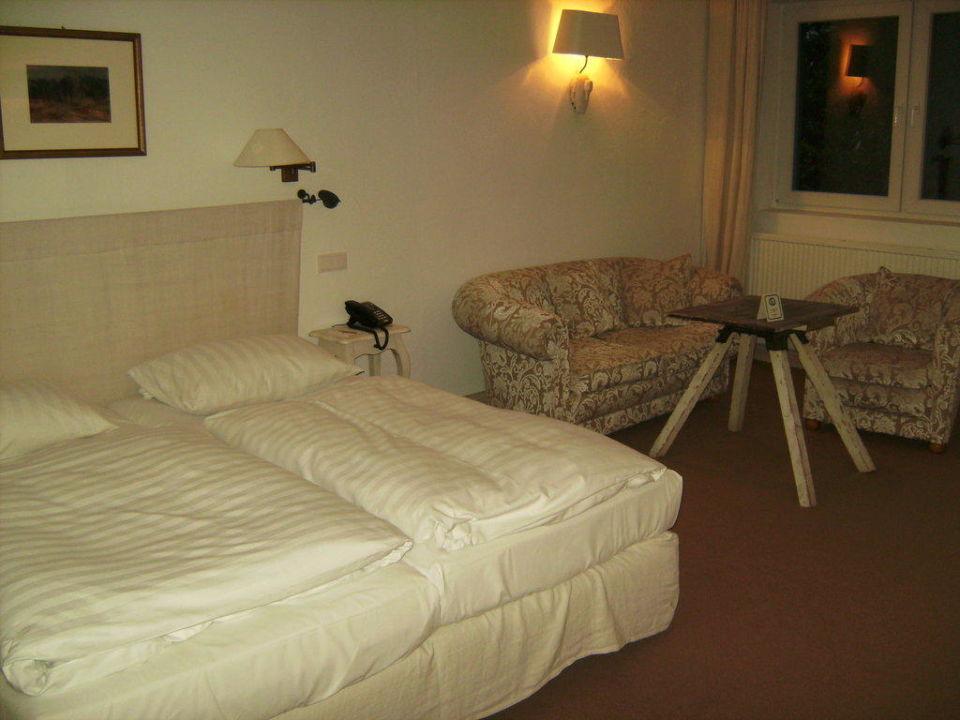 Bett, Sitzecke und rustikaler Tisch Hotel Zur Linde