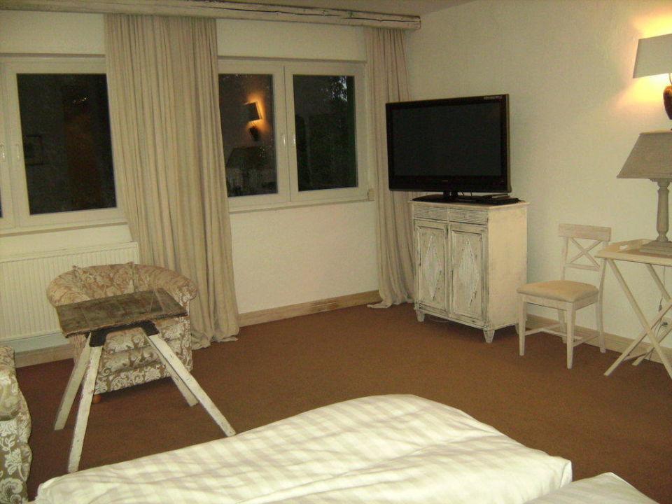 Bett, TV (darunter Minibar) und rustikaler Tisch Hotel Zur Linde