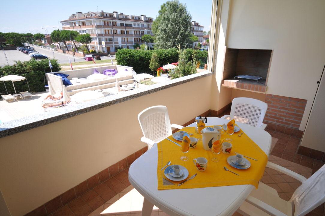 Terrazzo con tavolo, sedie e camino per barbecue\