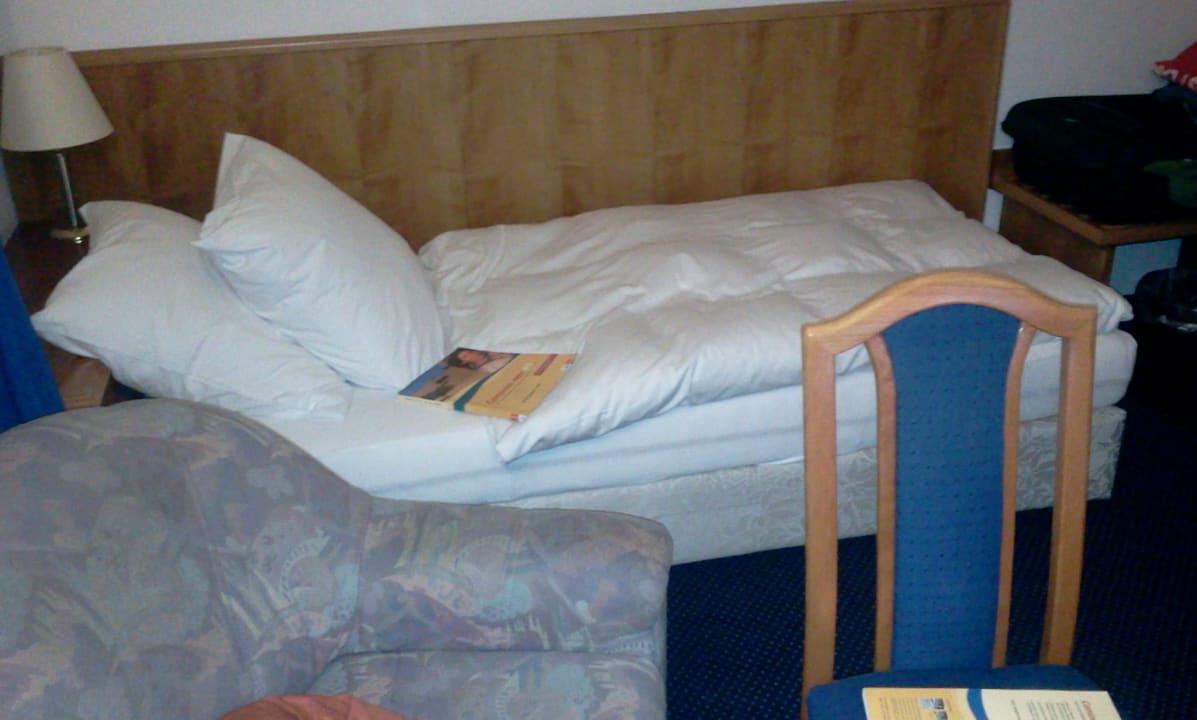 Blick auf Bett, Sessel und Stuhl Hotel Wester