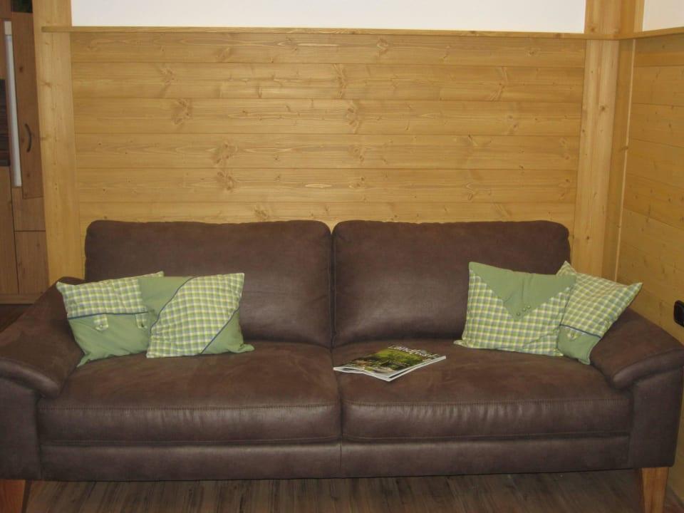 Couch vor rustikaler Holzwand in Fewo Untesberg Kochhof
