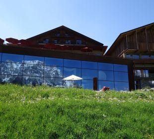 Die Zugspitze spiegelt sich von außen im Poolbereich Hotel Mohr Life Resort
