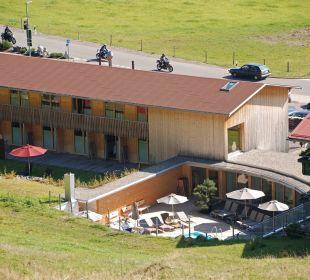 Blick vom Berg auf Poolbereich und Wellnesshaus Hubertus Alpin Lodge & Spa