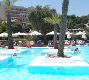 Widok z baru basenowego na basen - hotel w tle Hotel Grecotel Eva Palace