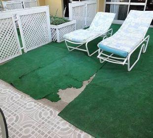 Auf der Terrasse ein zerfledderter Teppichbelag.