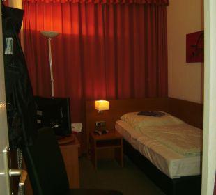 Bett, Nachttisch, kleiner TV auf Minibar, Stuhl Hotel John Brinckman
