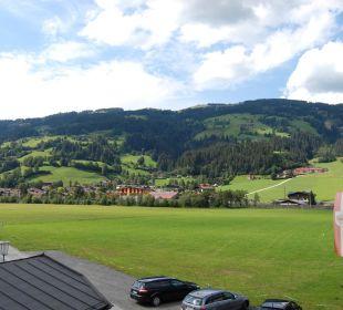 Blick vom Balkon auf Berge und Parkplatz Familienhotel Loipenstub'n