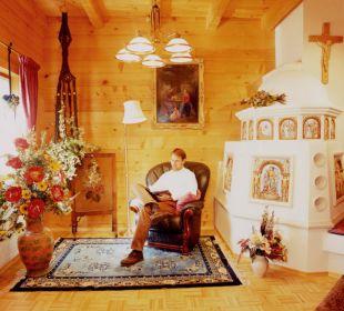 Gemütliche Leseecke beim Kachelofen mit Bibliothek Apartment Hotel Bio-Holzhaus Heimat
