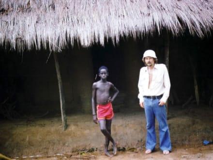 Jerzy mit einem Kind vor einer Savannenhütte - Stadtrundgang Saly