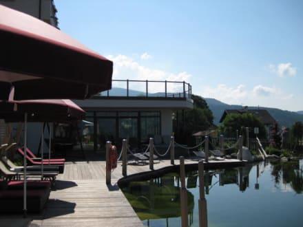 Naturbadeteich mit Liegen - Hotel Chalet Mirabell