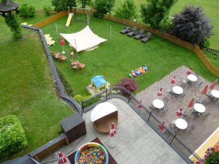 blick vom balkon zum garten mit sandkasten und co bild hotel babymio in kirchdorf tirol. Black Bedroom Furniture Sets. Home Design Ideas