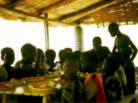 Dorfkinder beim Festessen - Stadtrundgang Saly