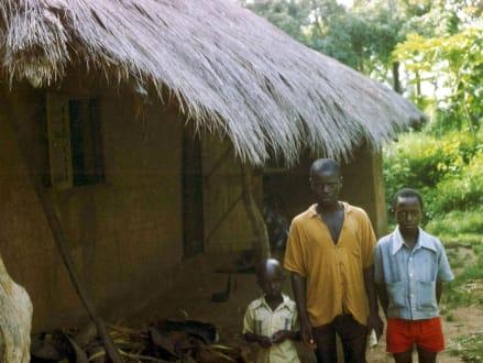 Drei Brüder vor einer typischen Savannenhütte - Stadtrundgang Saly