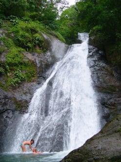 Baden im Wasserfall mit einem Abenteurer darüber - Adventure Tours